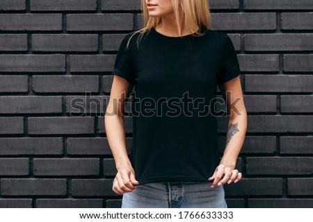 Stylish blonde girl wearing black t-shirt and glasses posing on black wall background, urban clothing style. Street photography Zdjęcia stock ©
