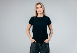 Stylish blonde girl wearing black t-shirt posing in studio