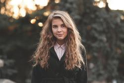 Stylish blonde teenage girl 15-16 year old wearing spring jacket posing outdoors close up. Looking at camera. Teenagerhood.