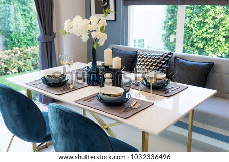 Stylish blue and white dining room with table set ready for a nice meal #1032336496