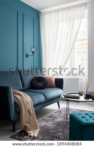 Stylish blue couch with decorative pillows, black coffee table and blue, square ottoman in small living room with window and molding on teal blue wall