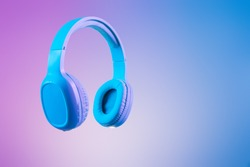 Stylish blue headphones on multi coloured / duo tone background lighting - lifestyle and fashion object concept image.