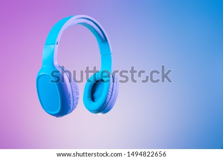 Stylish blue headphones on multi coloured / duo tone background lighting - lifestyle and fashion object concept image.