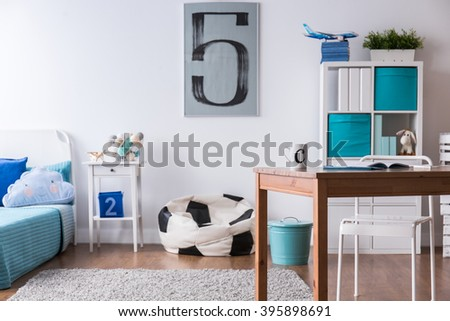 Stylish boy's room with wooden desk and pillow in football ball shape #395898691