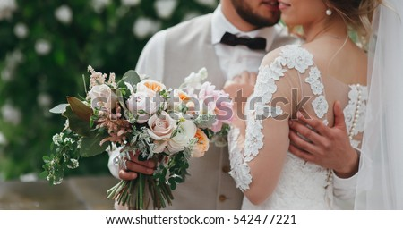 stylish bride and groom are holding bridal bouquet