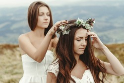 stylish bridesmaid helping gorgeous bride preparing, boho wedding, luxury ceremony at mountains