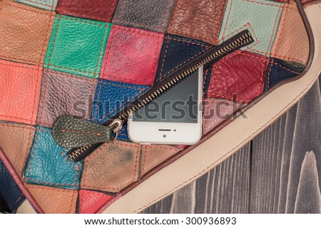 Stylish bright leather bag of square colorful patches. Close-up photo with pocket and zipper and a phone inside