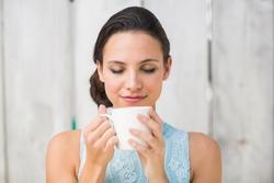 Stylish brunette holding a mug against bleached wooden fence