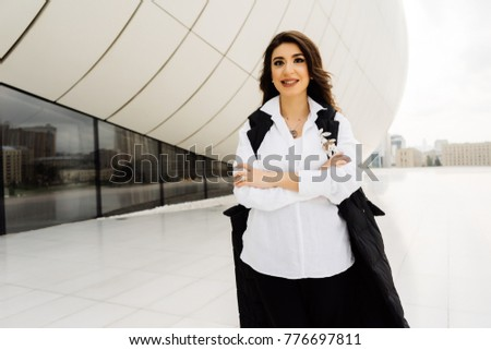 stylish brunette woman in black suit and white shirt posing against the background of the unusual architecture of Baku city