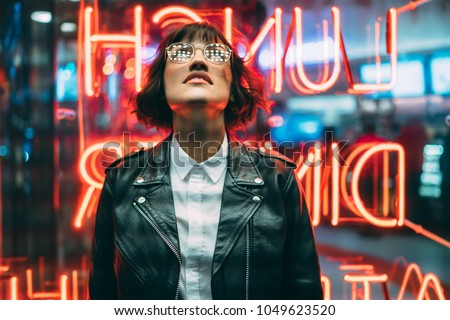 Stylish brunette woman in trendy apparel and eyewear looking up enjoying nightlife in city. Gorgeous fashion hipster girl in leather jacket standing outdoors on street with neon city illumination