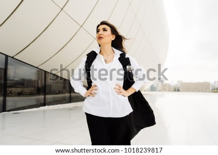 stylish business woman stands on building background