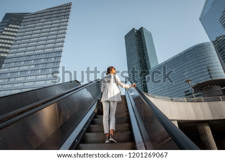 Stylish businesswoman in white suit going up on the escalator at the business centre outdoors with skyscrapers on the background in Paris #1201269067