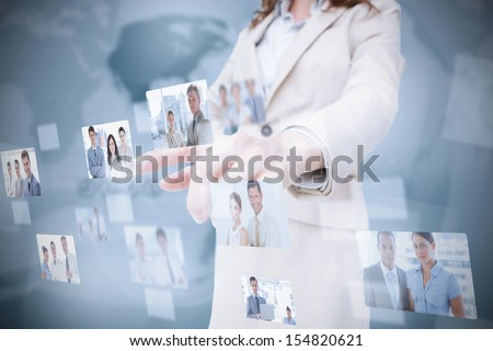 Stylish businesswoman presenting coworkers pictures on digital interface
