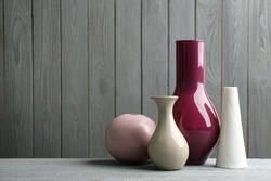Stylish ceramic vases on grey wooden table. Space for text