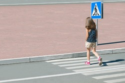 Stylish child in fashion clothes is walking along summer city crosswalk. Kid on pedestrian side walk. Concept pedestrians passing a crosswalk. Traffic rules. From top view. Shadow at zebra crossing