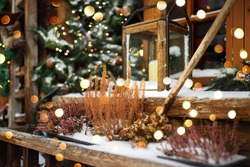 Stylish Christmas decorations near window - fir branches with garland lights and lantern with big candle on street in small town of Europe. Festive street decor and illumination in New Year holiday.