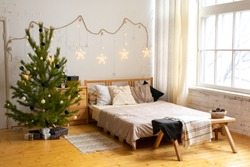 Stylish Christmas interior , bedroom with a lot of lights. Comfort home. Christmas decorated room in loft style.
