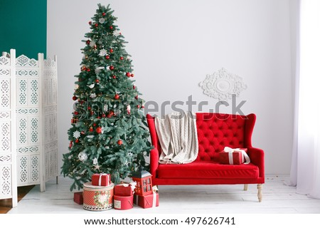 Stylish Christmas interior with an elegant red sofa. Comfort home. Armchair with fabric upholstery. Christmas tree with presents underneath in living room