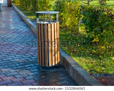 Stylish city urn made of wood and metal in the square. Comfortable urban environment