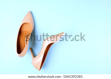Stylish classic women's beige leather shoes with medium high heels shot from top on pale blue background. Copy space, top view, flat lay. Shoe sale / clearance ad concept.