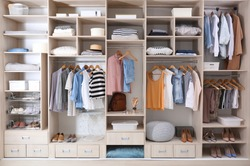 Stylish clothes, shoes and home stuff in large wardrobe closet