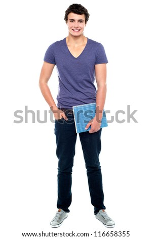 Stylish college student posing with notebook in one hand and other hand in  pocket