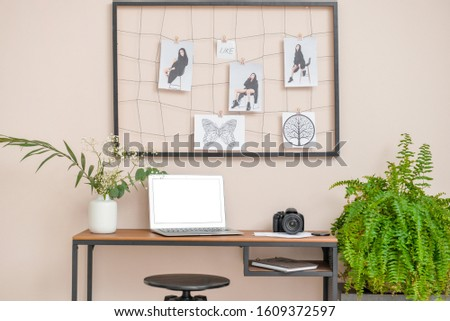 Stylish comfortable workplace with laptop, moodboard and photo camera in modern room