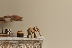 Stylish composition at moroccan interior with wooden shlef, cube, design elephant figure and decoration in modern home decor. Details. Template. Copy space.