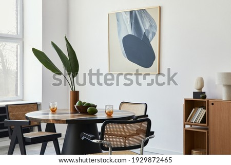 Stylish composition of dining room interior with design table, modern chairs, decoration, tropical leaf in vase, fruits, bookcase, abstract mock up paintings and elegant accessories in home decor. Stockfoto ©