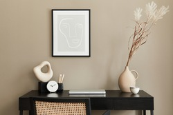 Stylish composition of home office interior with black wooden desk, chair, dried flower in vase, laptop, mock up poster frame, cup of coffee, clock and elegant office accessories. Template.