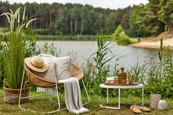 Stylish composition of outdoor garden on the lake with design rattan armchair, coffee table,  plaid, pillows, drinks and elegant accessories. Summer vibes.