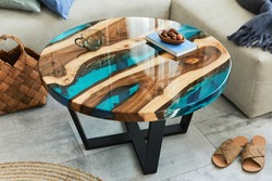 Stylish composition with design epoxy coffee table, sofa, blanket, pillows, book, decoration and personal accessories in modern home decor. Template. Details.