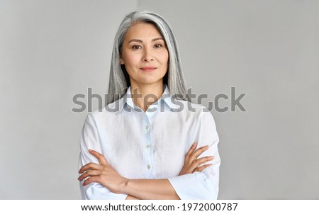 Stylish confident adult 50 years old Asian female psychologist standing arms crossed looking at camera at gray background. Portrait of sophisticated grey hair woman advertising products and services.