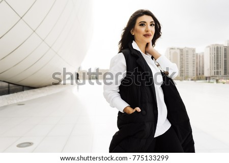 stylish confident girl in a black suit posing against the backdrop of unusual buildings in Baku, Azerbaijan