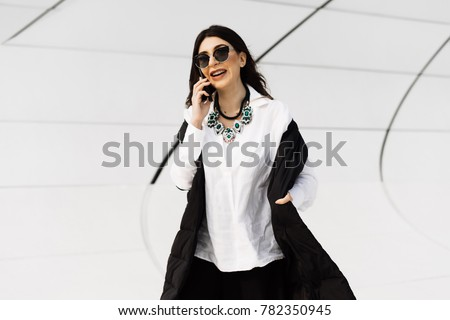 stylish confident woman in black suit and shirt talking on the phone