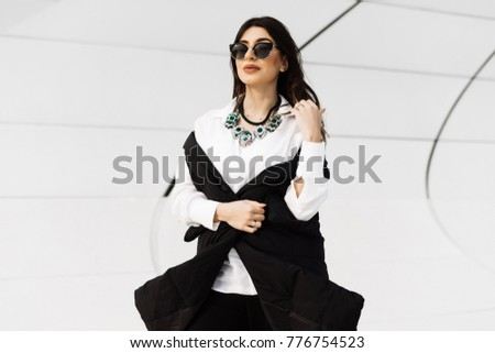 stylish confident woman in black suit and sunglasses posing, in Baku