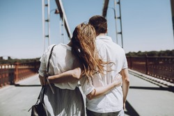 stylish couple in love hugging, back view with windy hair, on bridge in the summer city. modern woman and man in fashionable white clothes embracing at the river, romantic moment