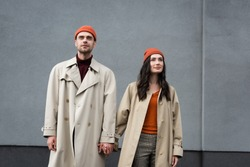 stylish couple in trench coats and hats standing and holding hands near grey wall outside
