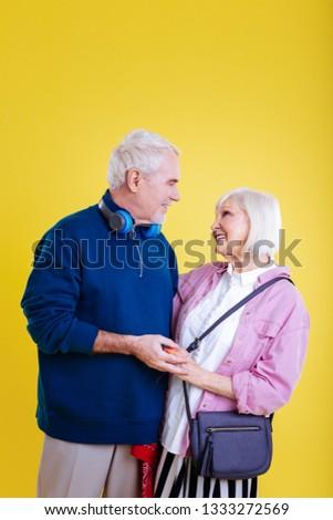 Stylish couple. Stylish retired woman wearing pink jacket looking at caring bearded husband