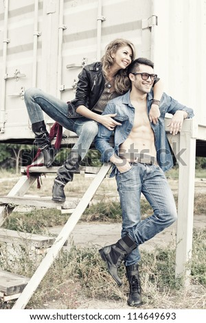 stylish couple wearing jeans and boots smiling - retro processed image