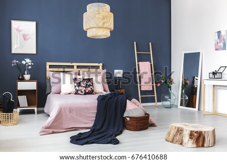 Stylish cozy hotel room with king-size bed and decorative wooden stump #676410688