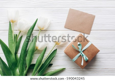 stylish craft present box and greeting card and tulips on white wooden rustic background. flat lay with flowers empty paper with space for text. hello spring concept. holiday gift #590043245