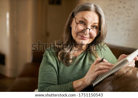 Stylish creative middle aged female writer or blogger in glasses sitting comfortably on couch with copybook and pen, handwriting, making notes, putting down ideas, thoughts, smiling at camera Photo stock ©