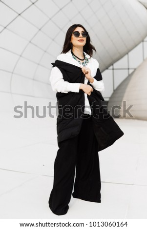 stylish dark-haired girl in black sunglasses and a black suit posing against the background of the unusual architecture of the city of Baku