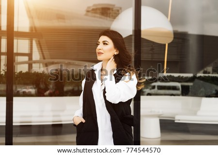 stylish dark-haired girl posing by the glass wall, in the city of Baku