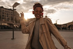 Stylish dark-skinned woman in beige trench coat dancing, smiling and listening to music in red headphones outside.