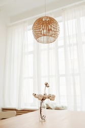 stylish decor minimalist boho style. bouquet natural cotton inglass vase on table next to huge window with white curtains and bamboo eco chandelier. ready-to-print interior poster, selective focus