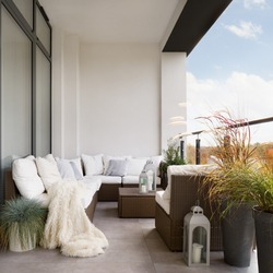 Stylish decorated balcony with rattan outdoor furniture, bright pillows, fluffy blanket and plants