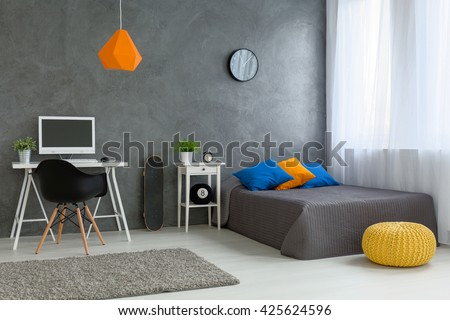 Stylish designed boy teenager\'s bedroom with grey walls and white furniture and colorful decorations