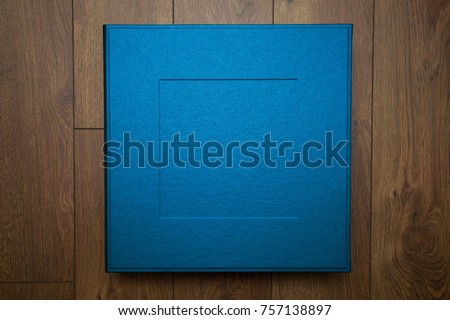 stylish designer square box for photo books on the wooden background with space for text cardboard box for a photo album. Box for wedding album on the wooden background. Gift box with lid.